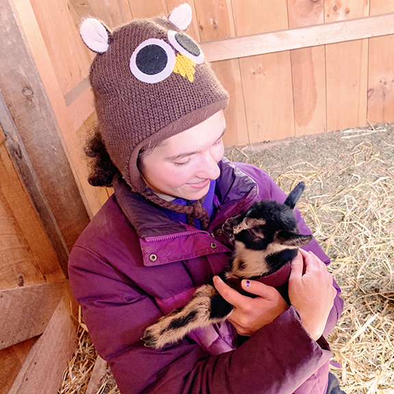 Harley holding newborn baby goat