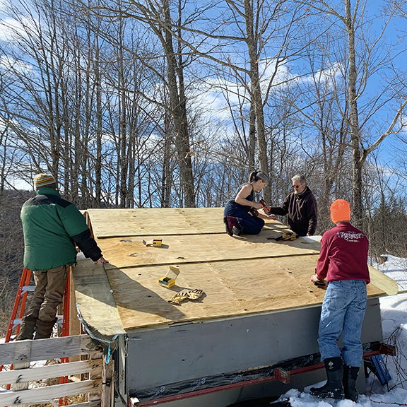 Many hands repair Stowe Farm Community's turkey tractor roof